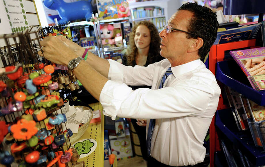 Connecticut Gov. Dannel P. Malloy purchases a bell that encourages kindness from the Ben's Bells organization as toy store owner Tracy Schmid looks on, in the business district of Sandy Hook in Newtown, Conn., Wednesday, July 31, 2013. Malloy is visiting to meet with business owners and talk about economic recovery after the December elementary school shooting that killed 20 students and six adults. (AP Photo/Jessica Hill) / FR125654 AP