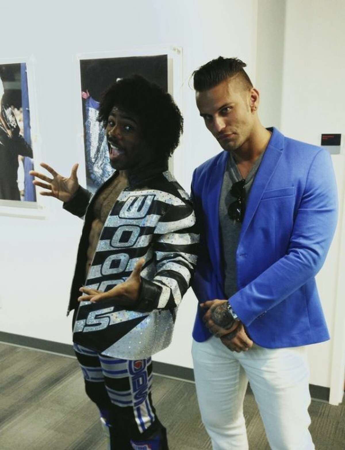 In this July 31, 2013 photo, wrestlers Xavier Woods, left, and Corey Graves pose inside the new World Wrestling Entertainment Performance Center in Orlando, Fla. The $2.5 million, 26,000-square foot facility opened in July, replacing a smaller, antiquated facility in Tampa, Fla. The facility is both a graduate school and a training and rehabilitation center. (AP Photo/Kyle Hightower)