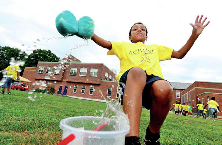 Hour photo / Erik TrautmannJayden McCollum participates in the Sponge Relay during the annual ACHIEVE Day/Field Day for summer camp at the Tracey School Wednesday. This year the program serviced over 170 students from Fairfield County with a variety of activities such as Leggo Robotics, yoga, cooking, academics (math,reading comprehension, and writing), and arts and crafts. / (C)2013, The Hour Newspapers, all rights reserved