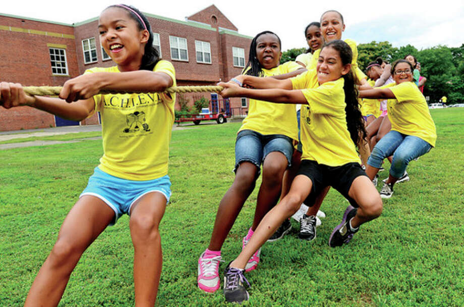 Hour photo / Erik TrautmannBetsy Burke, Amy Traore, Ashley Wilson and the rest of their team compete in a tug-a-war during the annual ACHIEVE Day/Field Day for their summer camp at the Tracey School Wednesday. / (C)2013, The Hour Newspapers, all rights reserved