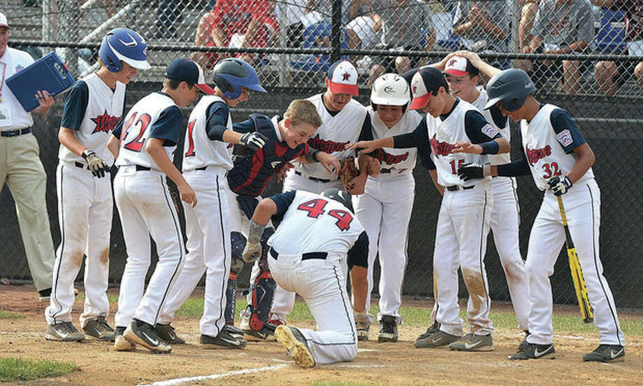 Hour Photo/Alex von KleydorffWestport's Matthew Brown (44) touches home plate after hitting a home run as he greeted by teammates during Wednesday's 10-4 victory over Newton, Mass., at Breen Field in Bristol. The win was Westport's fourth in four games at the New England Regional tournament and gave it the top seed in Thursday's semifinal elimination game.
