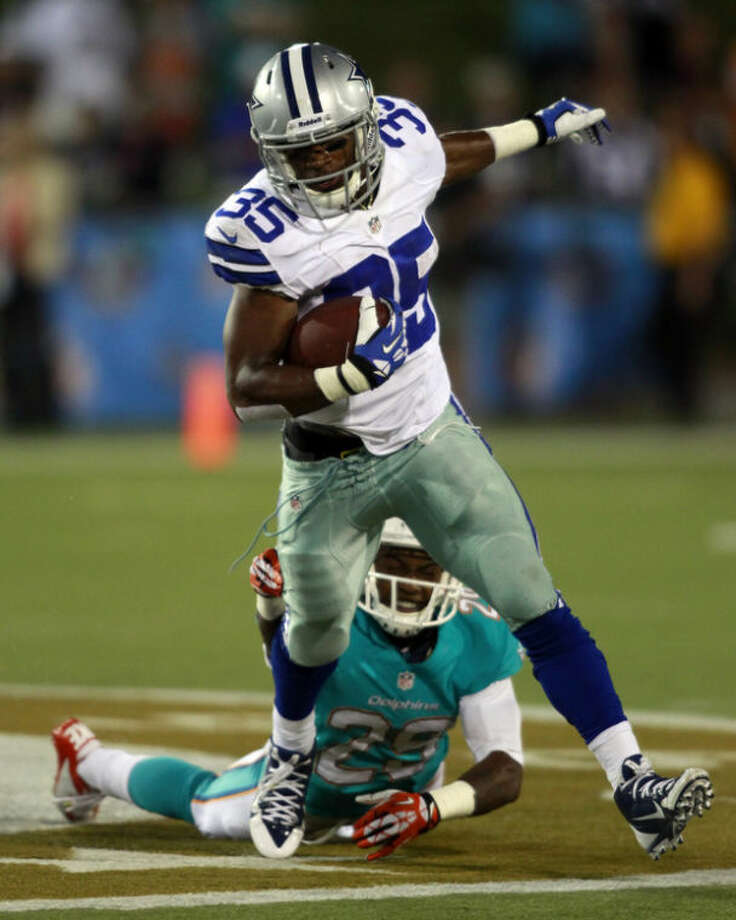 Dallas Cowboys running back Joseph Randle (35) breaks a tackle from Miami Dolphins cornerback Will Davis (29) and runs for 10 yards in the third quarter of the Pro Football Hall of Fame exhibition football game, Sunday, Aug. 4, 2013, in Canton, Ohio. (AP Photo/Scott R. Galvin)