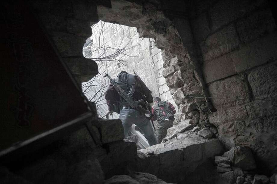 In this Saturday, Nov. 03, 2012 photo, rebel fighters sneak through residential buildings as they try to repel a coordinated attack using mortar, tank and aerial artillery carried out by loyalists to President Bashar Assad in the Jedida district of Aleppo, Syria. (AP Photo/Narciso Contreras) / AP