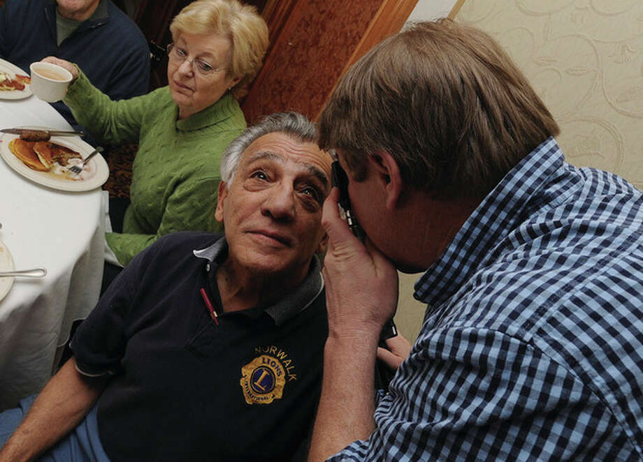 Hour photo /Matthew VinciLions Club member Ed Farris gets his eyes checked by DavidMcCullough, MD, Sunday at the Norwalk Inn and Conference Center during the Lions Club annual pancake breakfast. / (C)2011 {your name}, all rights reserved