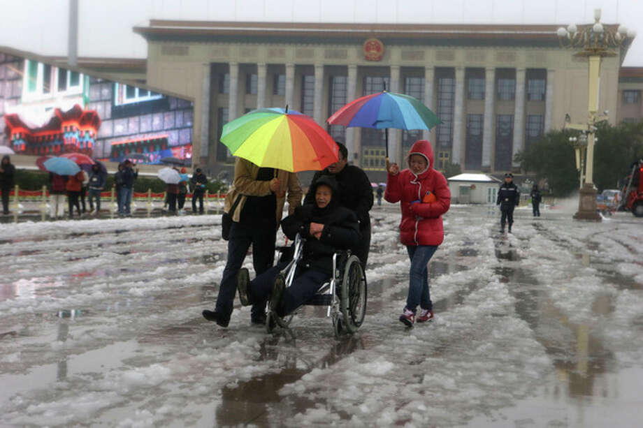 An elderly Chinese man is pushed in an wheelchair near the Great Hall of the People where the Chinese Communist Party's 18th National Congress is scheduled to begin on Nov. 8 in Beijing, China, Sunday, Nov. 4, 2012. The once-a-decade event installs a new leadership to run the world's second largest economy and newly assertive global power. (AP Photo/Ng Han Guan) / AP
