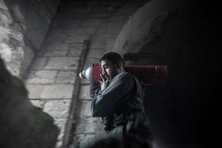 In this Saturday, Nov. 03, 2012 photo, a rebel fighter carries an improvised explosive device as they try to repel a coordinated attack using mortar, tank and aerial artillery fire carried out by loyalists to President Bashar Assad in the Jedida district of Aleppo, Syria. (AP Photo/Narciso Contreras) / AP