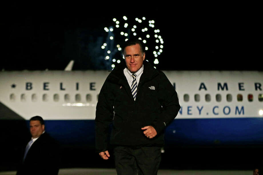 Fireworks explode in the distance as Republican presidential candidate and former Massachusetts Gov. Mitt Romney walks on stage at a Virginia campaign rally at Newport News International Airport, in Newport News, Va., Sunday, Nov. 4, 2012. (AP Photo/Charles Dharapak) / AP