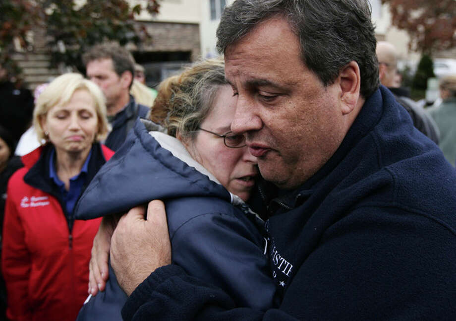 New Jersey Gov. Chris Christie tries to comfort Alice Cimillo and other Moonachie, N.J. residents whose homes were damaged by Superstorm Sandy, Thursday, Nov. 1, 2012, during a tour of the flood-ravaged area. The flooding of Moonachie, Little Ferry and Carlstadt, three communities sandwiched between Teterboro Airport, MetLife Stadium and the Hackensack River, was caused by six dirt berms that broke from the pressure of a tidal surge, Christie said. More than 1.7 million customers in New Jersey remain without power _ down from over 2.7 million at the height of the outages. (AP Photo/The Record of Bergen County, Kevin R. Wexler, Pool) / Pool The Record of Bergen County