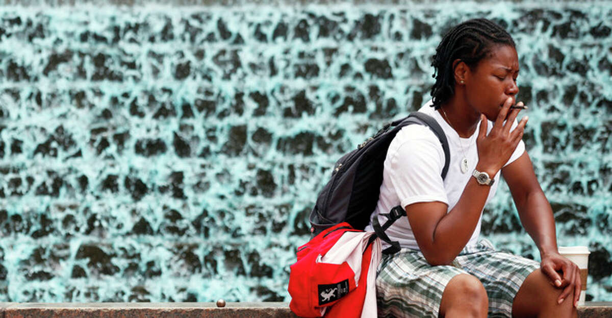"""Venisha Smalls, 35, of Atlanta, takes a smoke break next to a fountain in Woodruff Park, Friday, July 26, 2013, in Atlanta. """"No Smoking"""" signs are going up in parks, beaches and other outdoor venues across the country, but some experts are questioning whether there's enough medical evidence to support the trend. (AP Photo/Jaime Henry-White)"""