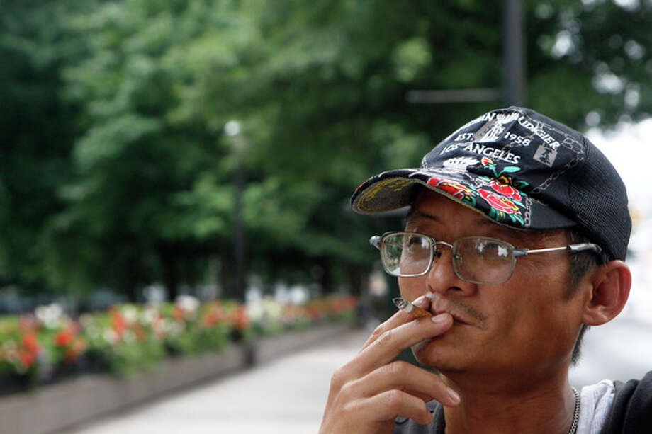"""Daniel Le, of Atlanta, smokes near the street next to Woodruff Park after being asked by a park ambassador to not smoke in the park, Friday, July 26, 2013, in Atlanta. """"No Smoking"""" signs are going up in parks, beaches and other outdoor venues across the country, but some experts are questioning whether there's enough medical evidence to support the trend. (AP Photo/Jaime Henry-White) / AP"""