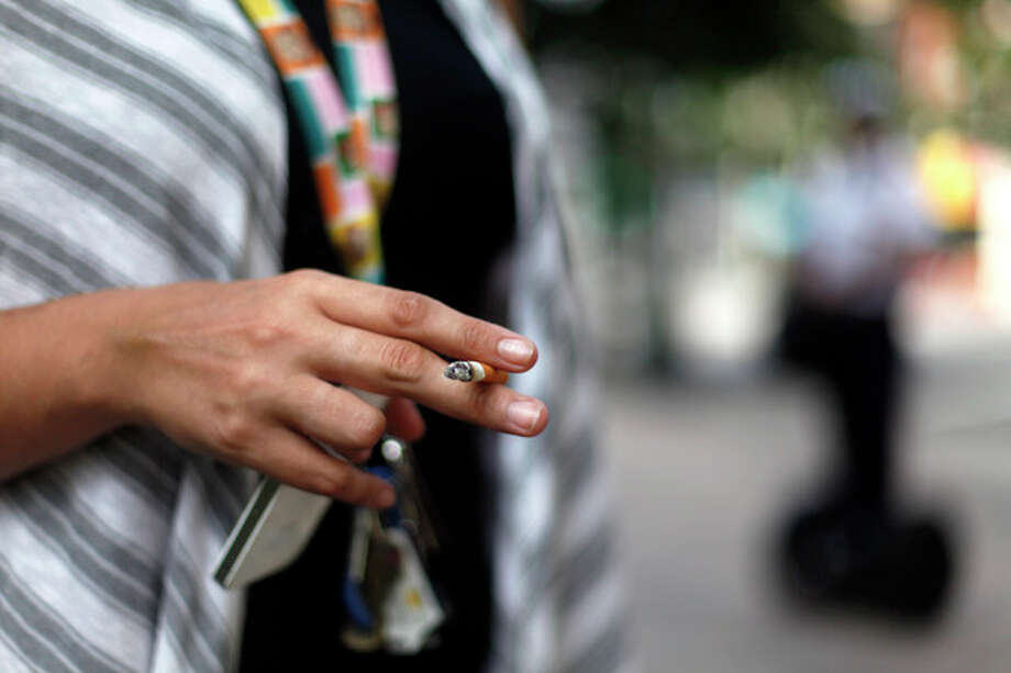 "Brianna Mills, 26, a nursing student from Marietta, Ga., smokes next to Woodruff Park as a park ambassador passes by on the sidewalk, Friday, July 26, 2013, in Atlanta. ""No Smoking"" signs are going up in parks, beaches and other outdoor venues across the country, but some experts are questioning whether there's enough medical evidence to support the trend. (AP Photo/Jaime Henry-White) / AP"