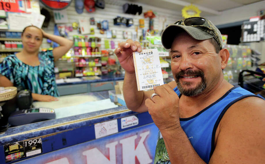 ADDS NUMBER OF WINNERS AND JACKPOT AMOUNT -Tony Valdez, right, shows off his Powerball lottery ticket he purchased from Vanessa Sanchez, left, Wednesday, Aug. 7, 2013, in San Antonio. Sue Dooley, senior drawing manager production coordinator for the Multi-State Lottery Association, said late Wednesday night that three tickets matched all six numbers and would split the $448 million Powerball jackpot. (AP Photo/Eric Gay) / AP