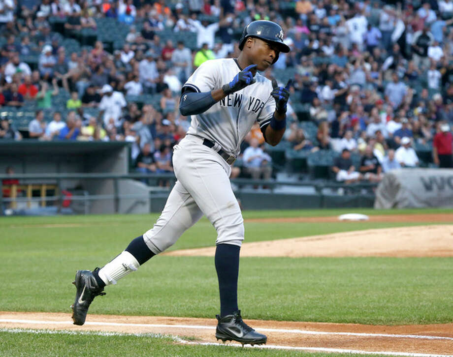 New York Yankees' Alfonso Soriano points to first base coach Mick Kelleher after hitting a two-run home run off Chicago White Sox starting pitcher Hector Santiago during the first inning of a baseball game on Wednesday, Aug. 7, 2013, in Chicago. (AP Photo/Charles Rex Arbogast) / AP