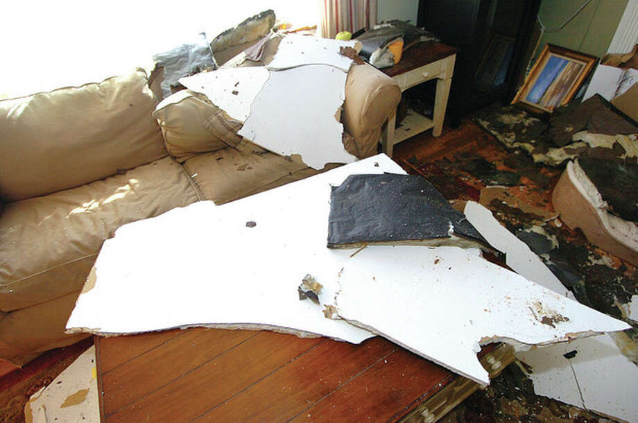 Hour Photo Alex von Kleydorff; Debris from the ceiling is scattered throuought the living room of Cyrus and Chrisine Karimi's house in Norwalk / 2012 The Hour Newspapers