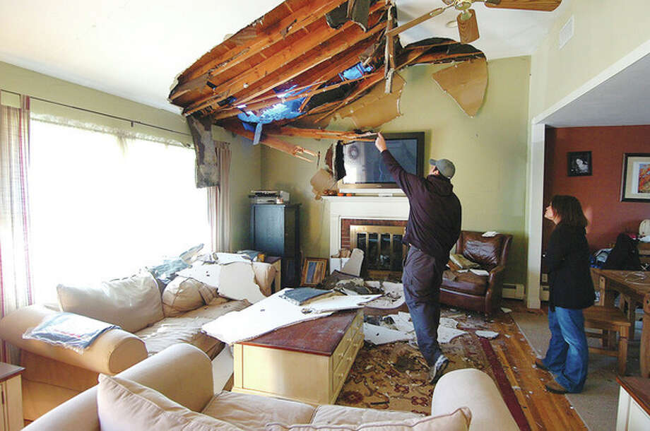 Hour Photo Alex von Kleydorff; Chrsitine and Cyrus Karimi survey their storm damaged living room in Norwalk. A large Oak tree was uprooted in their front yard and landed on their house causing extensive damage / 2012 The Hour Newspapers