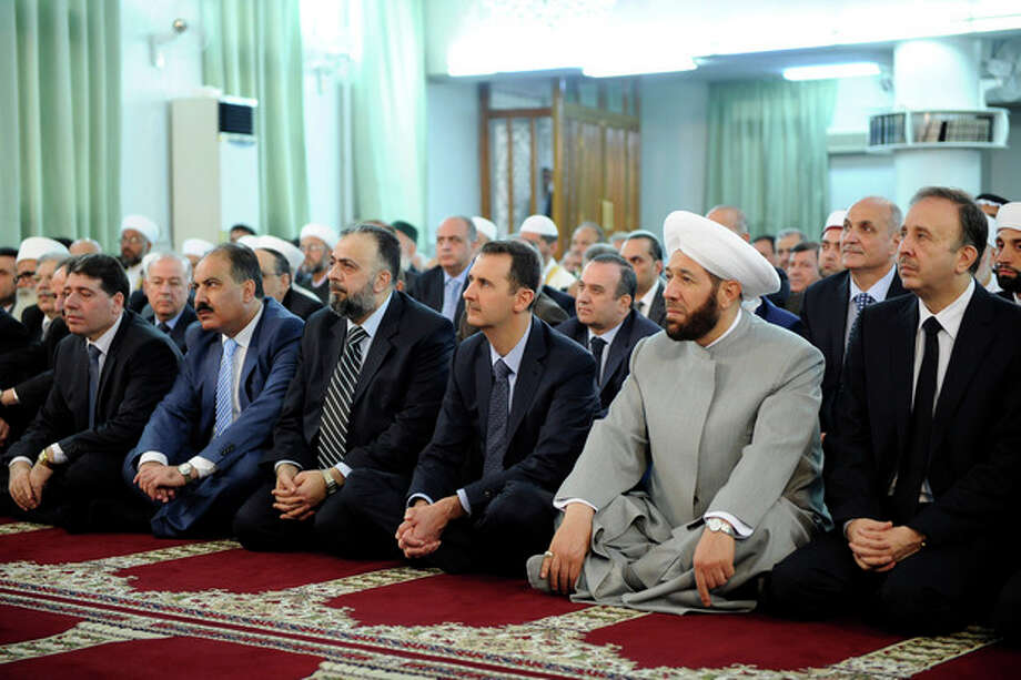 In this photo released by the Syrian official news agency SANA, President Bashar Assad, third right in front row, alongside Syria's grand mufti, second right, prays at the start of Eid al-Fitr, the three-day holiday that ends the holy month of Ramadan at the Anas bin Malik Mosque, Damascus, Syria, Thursday Aug. 8, 2013. Mortar rounds on Thursday hit an upscale district of Damascus where Assad attended prayers to mark the start of a major Muslim holiday in a rare attack in the high security area. (AP Photo/SANA) / SANA
