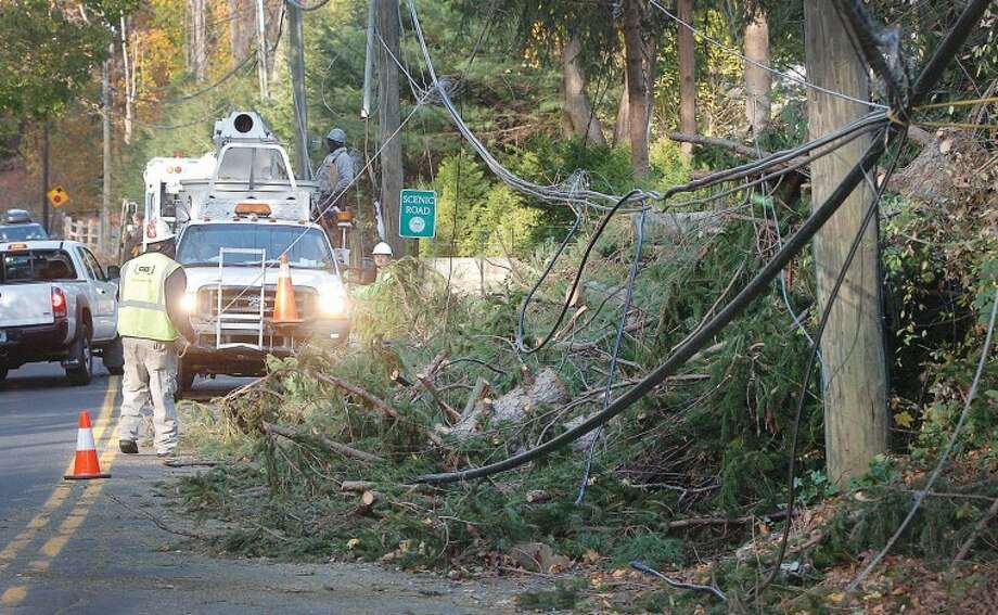 Hour Photo Alex von Kleydorff; Utility crews work on Nod Hill Rd near the intersection of Ridgefield Rd in Wilton on Monday