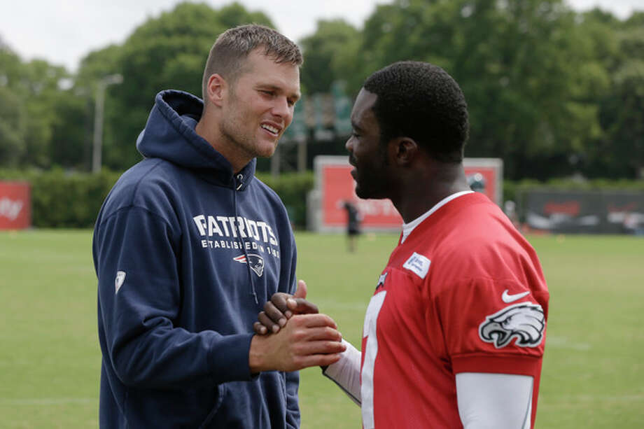 New England Patriots' Tom Brady, left, and Philadelphia Eagles' Michael Vick meet during a joint workout at NFL football training camp in Philadelphia, Thursday, Aug. 8, 2013. (AP Photo/Matt Rourke) / AP