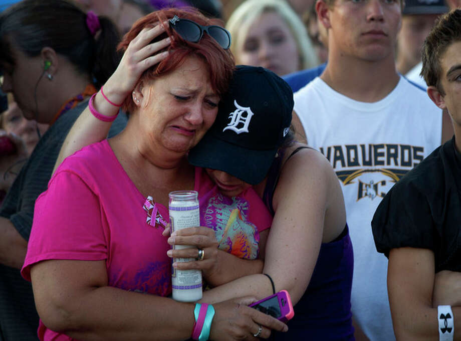 Missing children Hannah and Ethan Anderson's aunt Jennifer Willis, left, and cousin Hallie Landy embrace during an emotional candelight vigil Tuesday evening, Aug. 6, 2013, at El Capitan High School in Lakeside, Calif. Authorities found Christina Anderson's body Sunday in a home in Boulevard, Calif., 65 miles east of San Diego. Her children were missing and one or both may have been abducted. (AP Photo/U-T San Diego, ) NO SALES; COMMERCIAL INTERNET OUT / UTI1728631