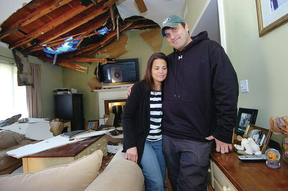 Hour photo / Alex von KleydorffChrsitine and Cyrus Karimi stand in their storm-damaged home in Norwalk. A large oak tree was uprooted in their front yard and landed on their house causing extensive damage. / 2012 The Hour Newspapers