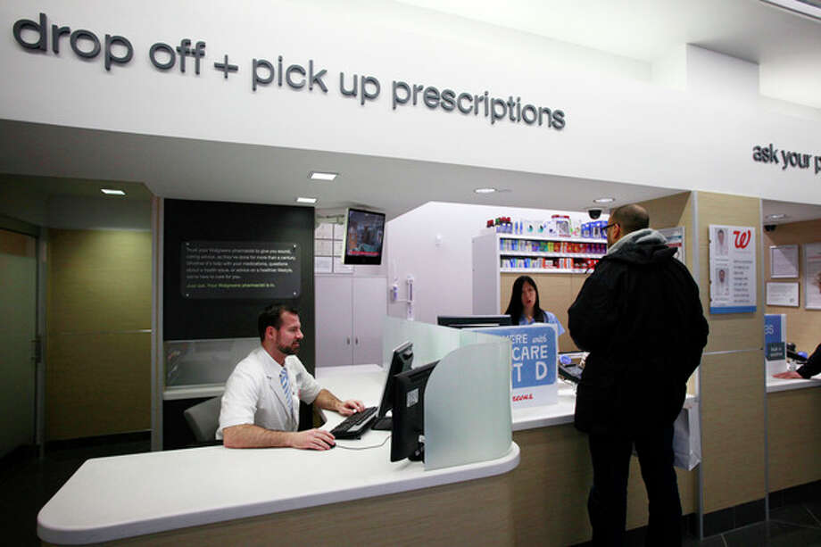 In this Wednesday, May 15, 2013, photo, Pharmacist Dan Darlington works at his desk located next to the prescription pick up counter at the Walgreens flagship store in the Empire State Building, Wednesday, May 15, 2013 in New York. The pharmacy is designed to encourage greater interaction between pharmacists and patients. (AP Photo/Mark Lennihan) / AP