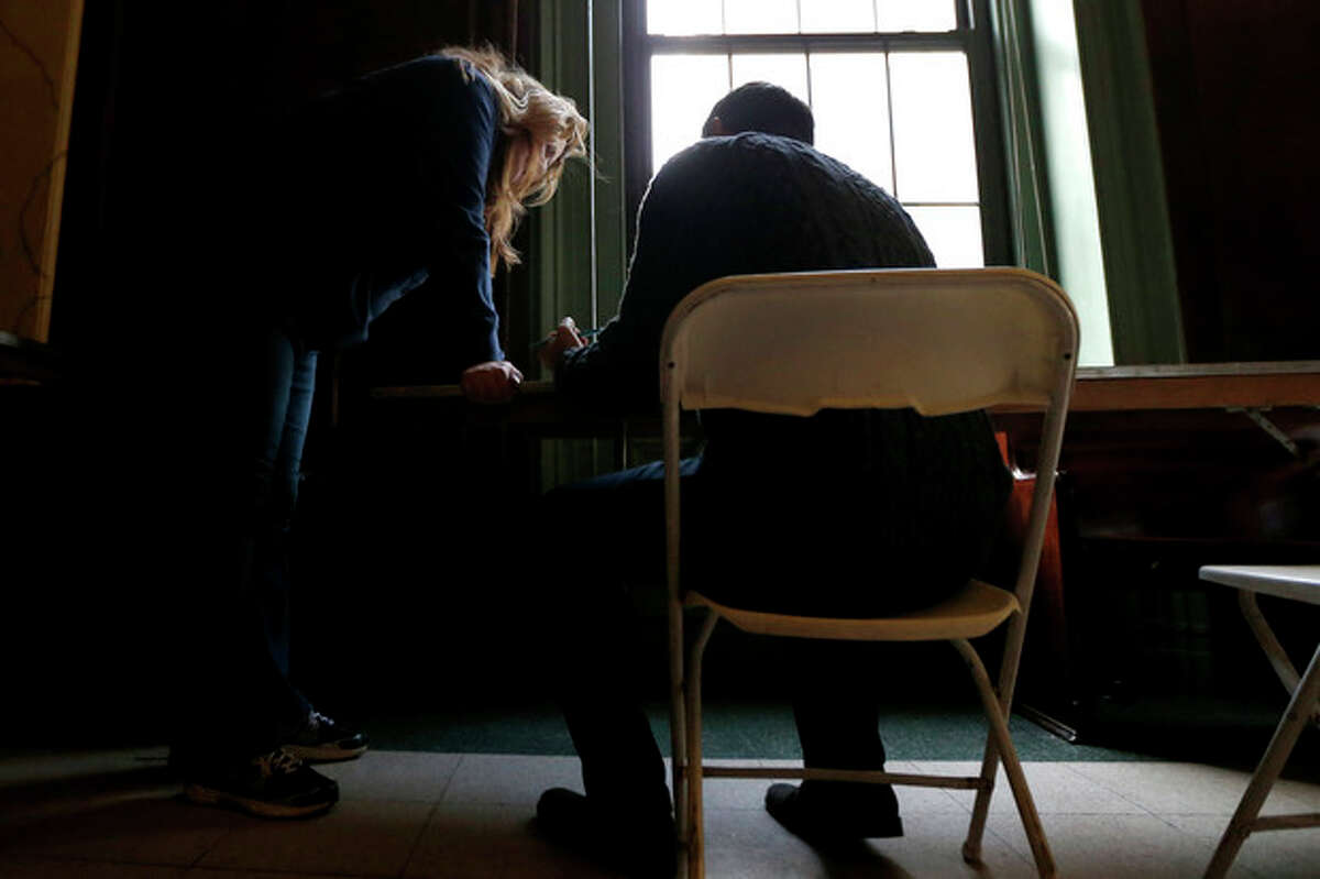 A polling place worker, left, assists a person who is filling out a affidavit to vote in the general election on Election Day, Tuesday, Nov. 6, 2012, in Hoboken, N.J. New Jersey Gov. Chris Christie signed a declaration allowing people displaced by Superstorm Sandy to vote in the general election at any polling place. However, such voters were not allowed to vote in local elections. (AP Photo/Julio Cortez)