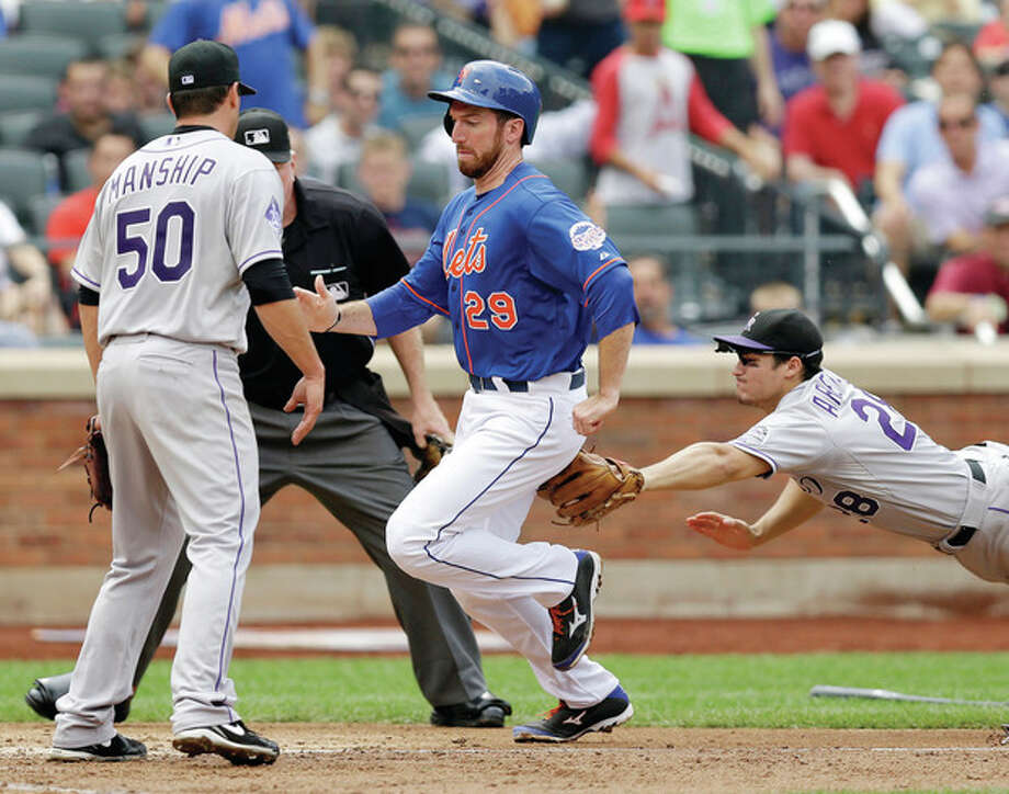 Colorado Rockies pitcher Jeff Manship (50) watches as Colorado Rockies third baseman Nolan Arenado (28) tags out New York Mets Ike Davis (29) after Davis was caught in a rundown between third and home in the fourth inning of a baseball game in New York, Thursday, Aug. 8, 2013. (AP Photo/Kathy Willens) / AP