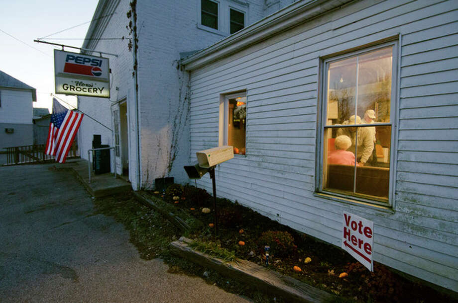 People sign in to vote Tuesday, Nov. 6, 2012 at the Elizaville precinct in Elizaville, Ky. The precinct is located in a general store built in 1821 and has 524 registered voters. (AP Photo/John Flavell) / FR44648 AP