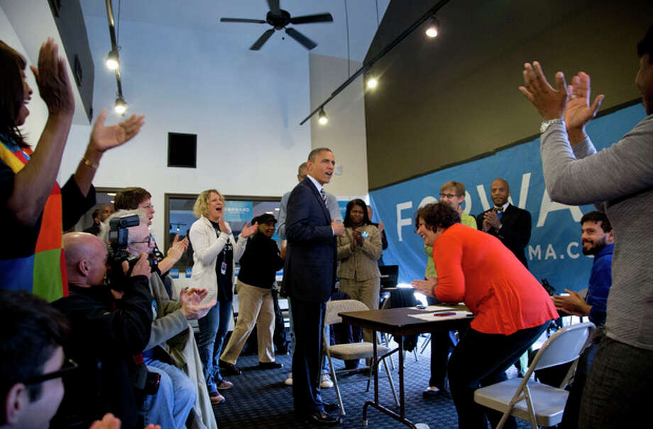 President Barack Obama is applauded as he visits with volunteers at a campaign office the morning of the 2012 election, Tuesday, Nov. 6, 2012, in Chicago. (AP Photo/Carolyn Kaster) / AP
