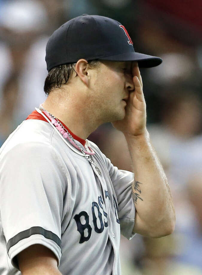 Boston Red Sox's Steven Wright wipes his face after Houston Astros' Jason Castro scored a run in the first inning of a baseball game Tuesday, Aug. 6, 2013, in Houston. Wright only pitched the one inning, giving up three runs on one hit. (AP Photo/Pat Sullivan)