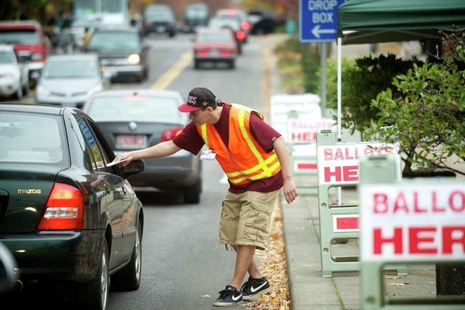 Clark County elections official Miguel Rivera takes ballots from motorists outside the Clark County Elections office Tuesday Nov. 6, 2012 in Vancouver, Wash. (AP Photo/The Columbian, Troy Wayrynen) / The Columbian
