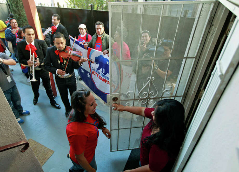 "Rosanna Del Rio, left, greets registered voter Edna Hernandez as the mariachi band ""Gallos de Jalisco"" serenades voters Tuesday, Nov. 6, 2012 in Los Angeles. (AP Photo/Damian Dovarganes) / AP"