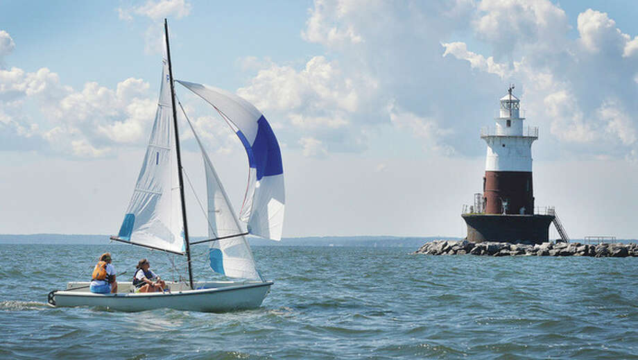Hour Photo/Alex von Kleydorff . Claire Wagner and Lindsay Walsh on the Norwalk Yacht Club entry set their spinnaker as they pass Greens Ledge lighthouse on Long Island Sound during the Pixel Championship on Tuesday