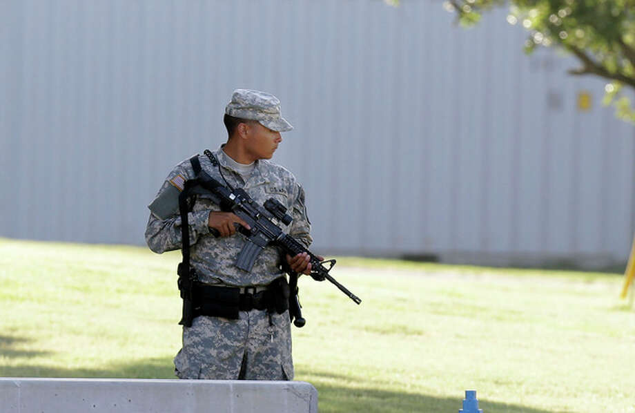 An armed soldier stands guard outside the courthouse where the court-martial of Maj. Nidal Malik Hasan is taking place Tuesday, Aug. 6, 2013, in Fort Hood, Texas. After years of delays, the trial of the man who carried out the Fort Hood shooting is starting, with Hasan representing himself against charges of murder and attempted murder for the 2009 attack that left 13 people dead on the Army post. (AP Photo/LM Otero) / AP