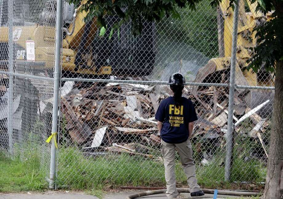 "An FBI agent watches as the house where three women were held captive and raped for more than a decade is being demolished Wednesday, Aug. 7, 2013, in Cleveland. Authorities want to make sure the rubble isn't sold online as ""murderabilia,"" though no one died there. The house was torn down as part of a deal that spared Ariel Castro a possible death sentence. He was sentenced last week to life in prison plus 1,000 years. Castro apologized but blamed his addiction to pornography. (AP Photo/Tony Dejak) / AP"