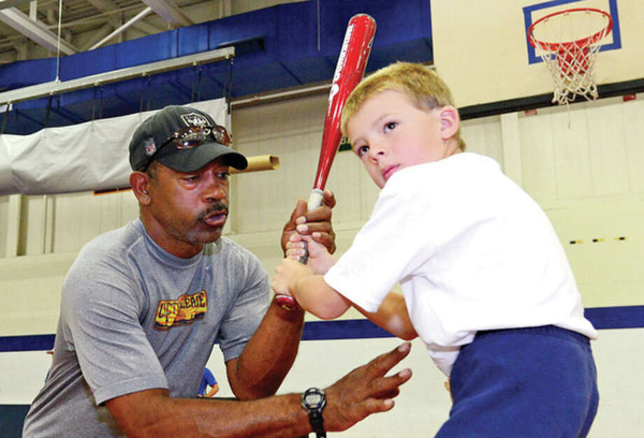 Hour photo/Erik TrautmannBridgeport Bluefish manager Willie Upshaw works with six-year-old Liam Kennedy during the Baseball World Camp on Friday at Staples High. Upshaw was a guest instructor at the camp, which attracts hundreds of campers during the multiple sessions every summer. / (C)2013, The Hour Newspapers, all rights reserved