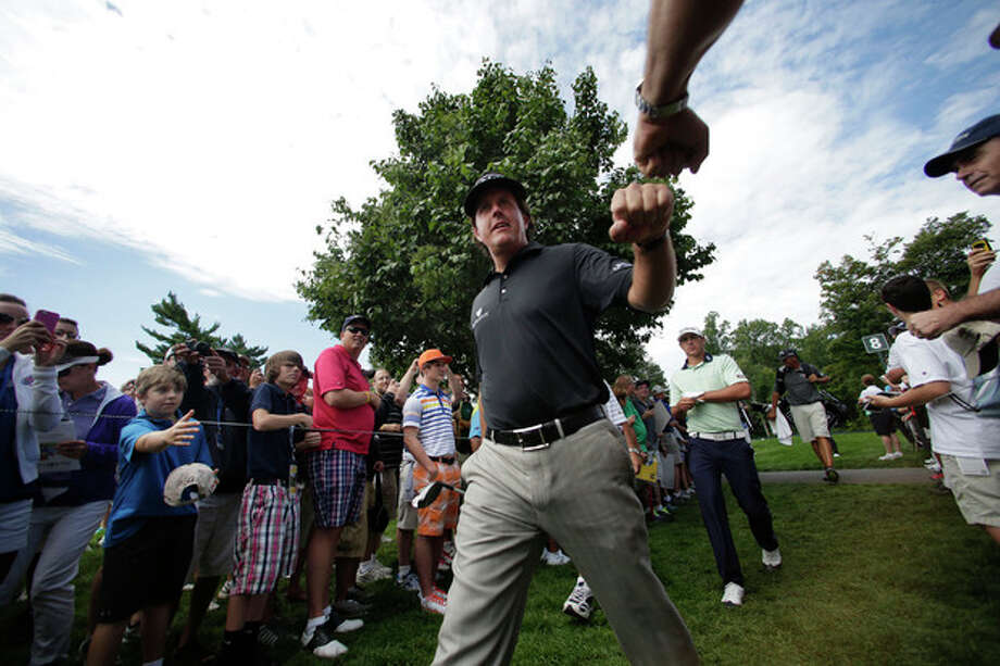 Phil Mickelson taps fists with a fan as he walks to the ninth tee during a practice round for the PGA Championship golf tournament at Oak Hill Country Club, Tuesday, Aug. 6, 2013, in Pittsford, N.Y. (AP Photo/Charles Riedel) / AP