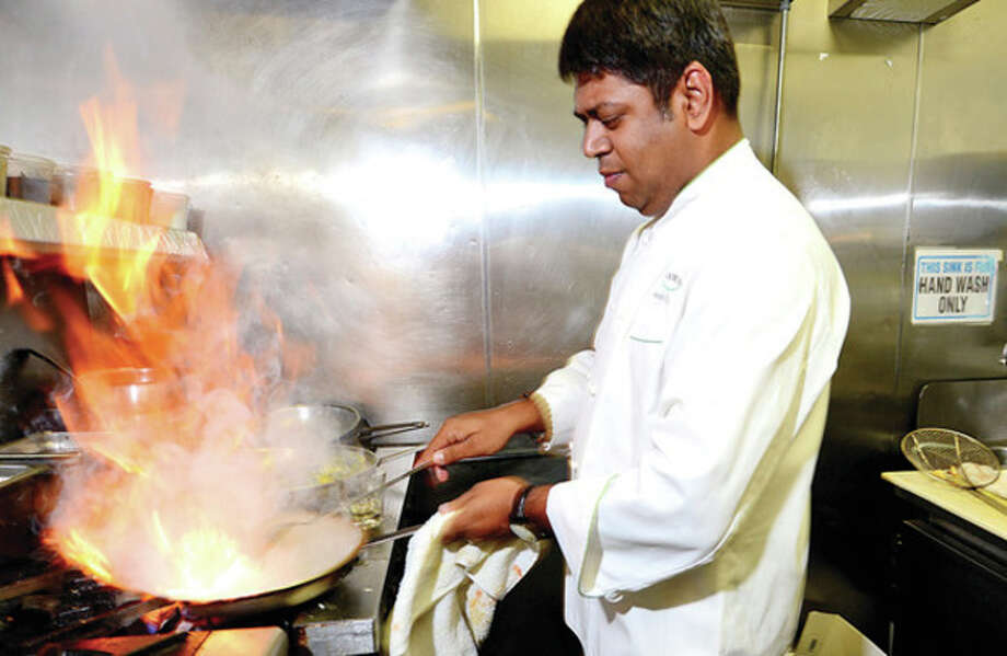 Kausik Roy, owner of Aladin Indian Bistro, works in the kitchen at the new restaurant on CT Ave. in Norwalk.Hour photo / Erik Trautmann / (C)2013, The Hour Newspapers, all rights reserved