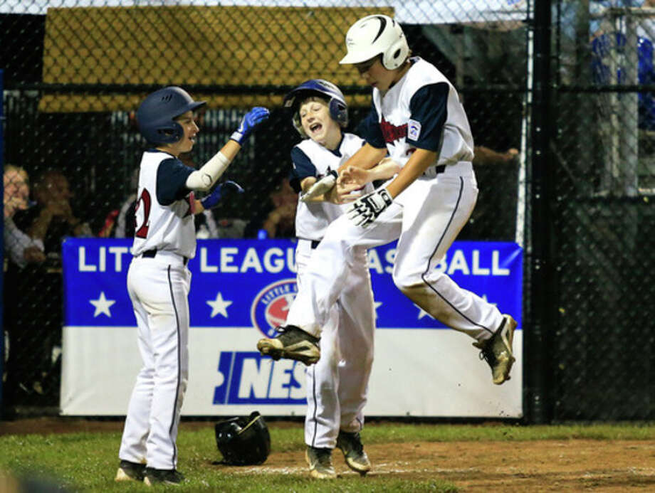 Hour photo/Chris PalermoWestport's Chad Knight leaps into his fellow teammates after scoring a run during the Little League Baseball New England Regional Tournament against South Berlington, Vt., on Friday, Aug. 2, at the Giamatti Little League Center in Bristol. Knight is slated to start Saturday night's New England Regional championship game against Lincoln, R.I. / © 2013 The Hour Newspapers All Rights Reserved