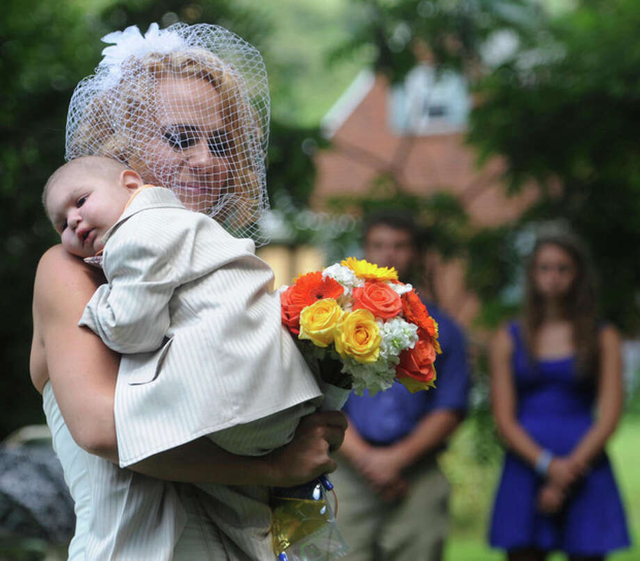 FILE - This Aug. 3, 2013 file photo, Christine Swidorsky carries her son and the couple's best man, Logan Stevenson, 2, down the aisle to her husband-to-be Sean Stevenson during the wedding ceremony in Jeannette, Pa. Christine Swidorsky Stevenson says on her Facebook page that Logan died in her arms at 8:18 p.m. Monday, Aug. 5, 2013, at their home in Jeannette, about 25 miles east of Pittsburgh. Logan, who was born Oct. 22, 2010, was diagnosed shortly after his first birthday with acute myeloid leukemia. The Stevensons abandoned an original wedding date of July 2014 after learning from doctors late last month that their son had two to three weeks to live. The couple wanted Logan to see them marry and to be part of family photos. (AP Photo/Tribune Review, Eric Schmadel) / Tribune Review