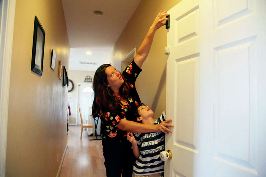 "Jo Ashline sets a door lock, accompanied by her son, Andrew, 11, who has autism, at their home in Orange, Calif. on Friday, Aug. 9, 2013. Ashline says, ""We take steps at home, locks on every door, gates, alarms but there's always, in the forefront of our minds, the thought that one tiny mistake could prove fatal."" The phenomenon goes by various names - wandering, elopement, bolting - and about half of autistic children are prone to it, according to research published in 2012 in the journal Pediatrics. It has claimed the lives of more than 60 children in the past four years and can make daily life a harrowing, never-let-your-guard-down challenge for parents whose sons and daughters are at risk. (AP Photo/Nick Ut) / The Grand Forks Herald"
