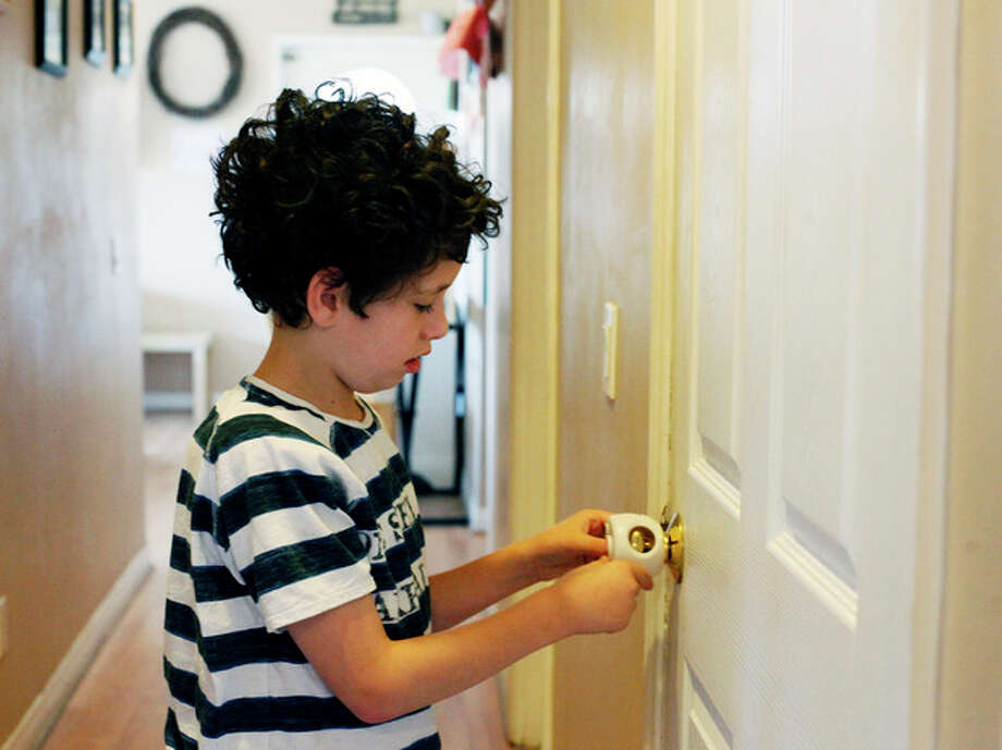 Andrew Ashline, 11, who has autism, tries to open a safety lock at the family home in Orange, Calif. on Friday, Aug. 9, 2013. Jo Ashline describes her home as resembling Fort Knox with its array of security measures aimed at deterring possible wandering by her son. (AP Photo/Nick Ut) / The Grand Forks Herald