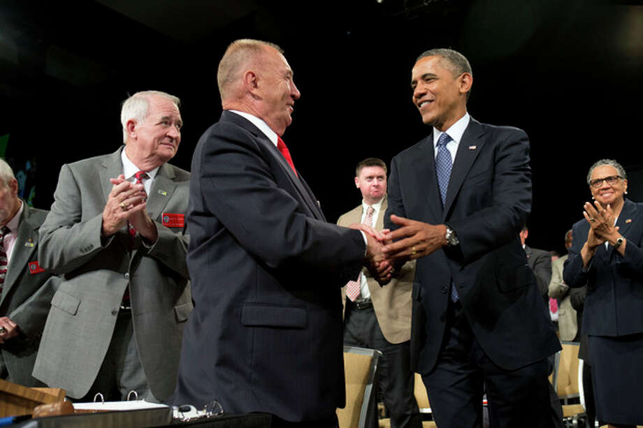 President Barack Obama shakes hands with Disabled American Veterans National Commander Larry Polzin, before speaking in Orlando, Fla., Saturday, Aug. 10, 2013. After the event the Obamas will travel to Martha's Vineyard, Mass. to begin their family vacation. (AP Photo/Jacquelyn Martin) / AP
