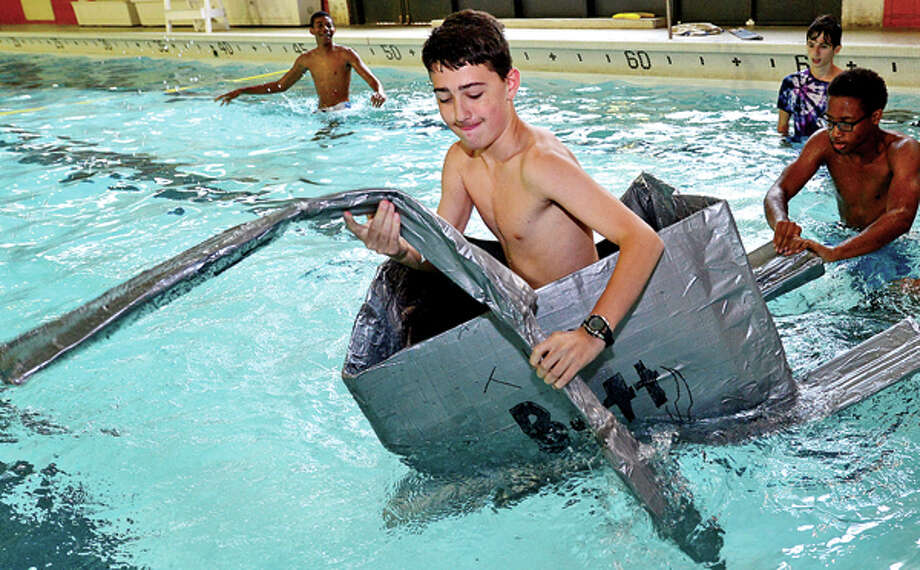 Incoming freshman Johnny Pesce races to the finish as Norwalk High School finishes up its Freshman Academy with a carboard and duct tape boat race in the Norwalk High swimming pool Friday. Hour photo / Erik Trautmann / (C)2013, The Hour Newspapers, all rights reserved