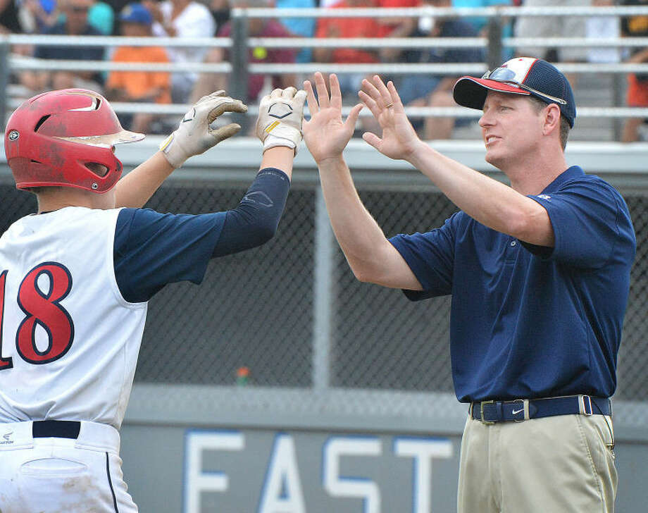 Hour Photo/Alex von Kleydorff. Coach Tim Rogers high fives Harry Azadian as he heads for home plate vs Newton