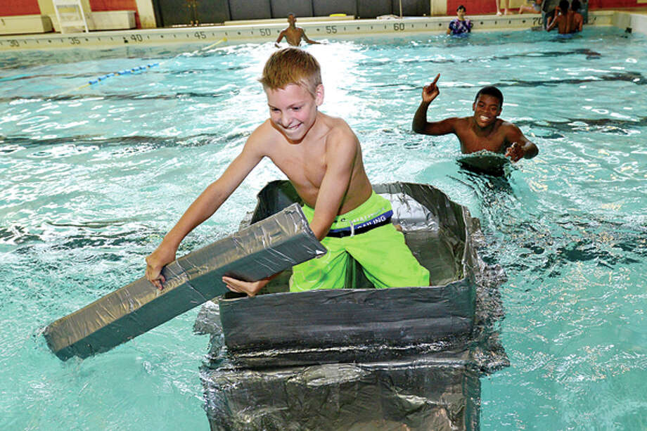 Incoming freshman John Smith races to the finish as Norwalk High School finishes up its Freshman Academy with a carboard and duct tape boat race in the Norwalk High swimming pool Friday. Hour photo / Erik Trautmann / (C)2013, The Hour Newspapers, all rights reserved