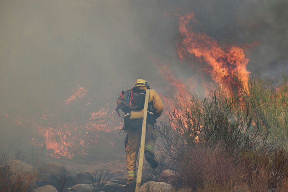 A firefighter battles a wildfire on Thursday, Aug. 8, 2013, in Cabazon, Calif. About 1,500 people have fled and three are injured as a wildfire in the Southern California mountains quickly spreads. Several small communities have evacuated.(AP Photo/Jae C. Hong) / AP