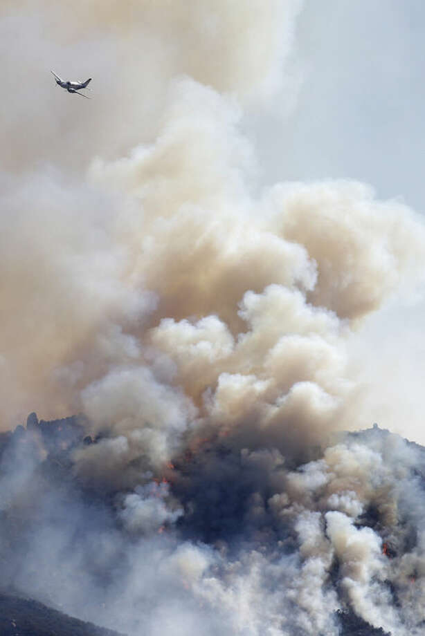 A small plane flies over a wildfire burning near Banning, Calif., on Thursday, Aug. 8, 2013. About 1,500 people have fled and three are injured as the wildfire in the Southern California mountains quickly spreads. Several small communities have evacuated. (AP Photo/Jae C. Hong)