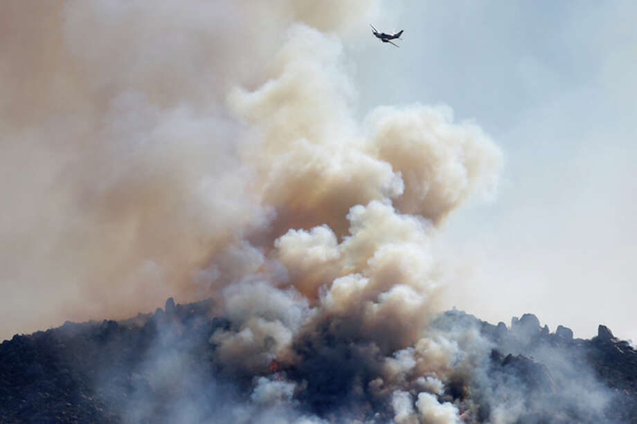A small plane flies over a wildfire burning near Banning, Calif., on Thursday, Aug. 8, 2013. About 1,500 people have fled and three are injured as a wildfire in the Southern California mountains quickly spreads. Several small communities have evacuated. (AP Photo/Jae C. Hong) / AP