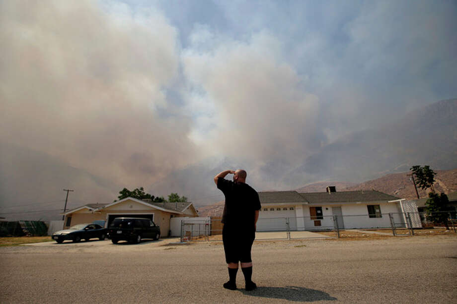 Robert Tucker watches a smoke from a wildfire on Thursday, Aug. 8, 2013, in Cabazon, Calif. About 1,500 people have fled and three are injured as a wildfire in the Southern California mountains quickly spreads. Several small communities have evacuated.(AP Photo/Jae C. Hong) / AP